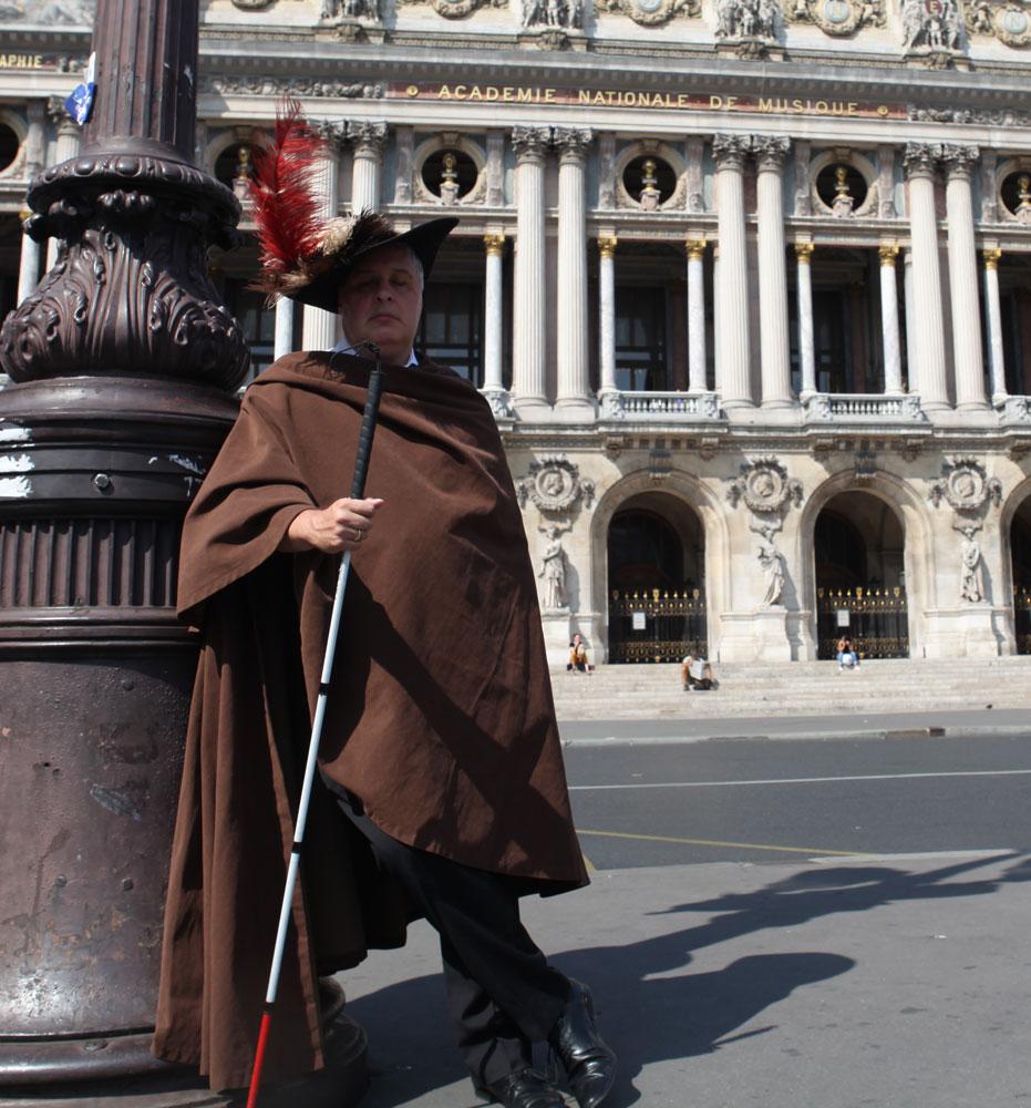 Image de Bertrand Bontoux. Il porte un costume de théatre, avec une grande cape marron, un chapeau à large bord avec des grandes plumes rouge et blanche, et tient une canne à la main, debout, appuyé contre un réverbère, devant l'Opéra Garnier de Paris.