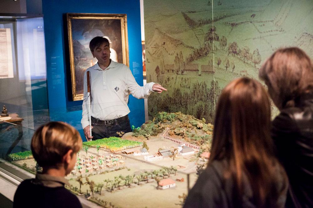 Image de Nicolas Caraty. Il se tient debout derrière un diorama de camp militaire, pointant des détails du doigt. Il tient sa canne dans sa main droite; il porte un polo blanc à manche longue et un jean noir. Au premier plan de l'image, on voit des visiteurs, de dos, en train de l'écouter.