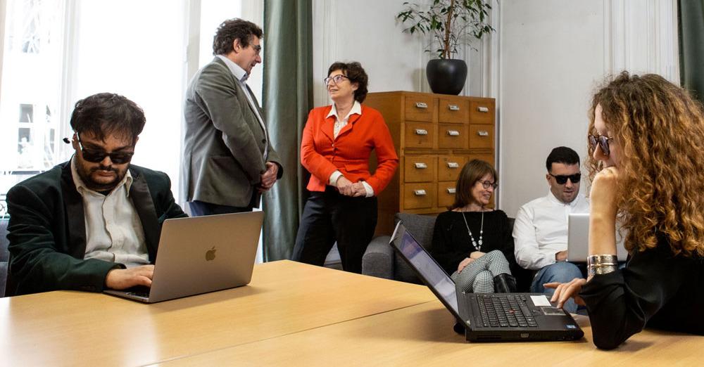 Image d'une réunion de travail chez actifsDV. Au premier plan, deux personnes, assises à une table, utilisent leurs ordinateurs; en arrière-plan, quatre personnes, par groupe de deux, discutent et échangent.