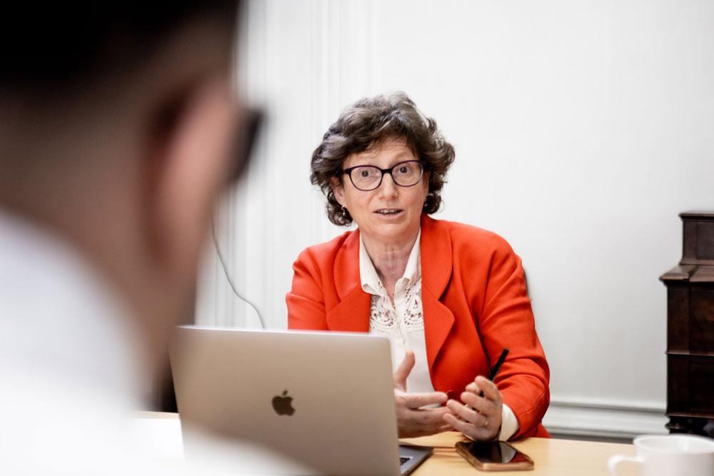 Image de Caroline Levy-Cosson, assise devant un ordinateur, en train de parler à un interlocuteur de dos, flou, au premier plan.