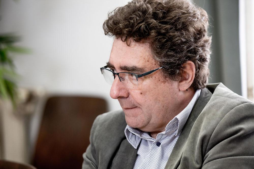 Image d'André Guadon, vu de profil, en plan serré; il regarde vers la gauche, porte des lunettes, une chemise bleue et une veste grise.