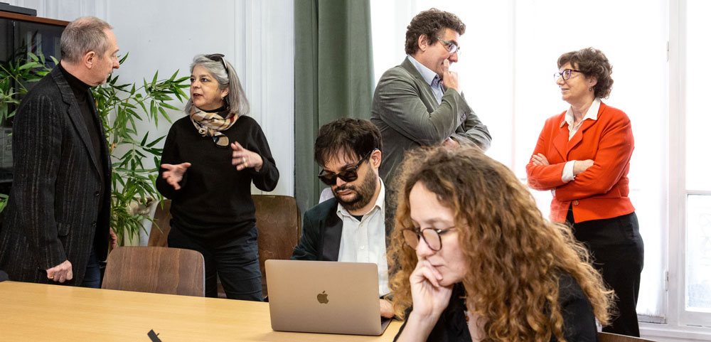 Picture of a work meeting at actifsDV. Three groups of two are in the picture; two groups of two are talking to each other in the background, while in the foreground, one is making a phone call, and another is using his computer.